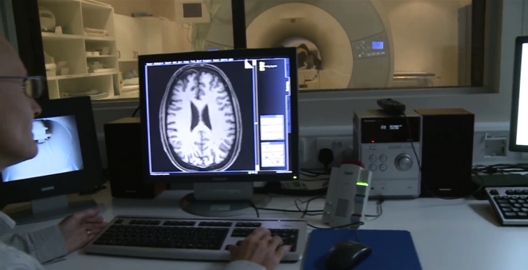 A researcher conducting an MRI - a brain scan displays on the computer screen with the machine in the background