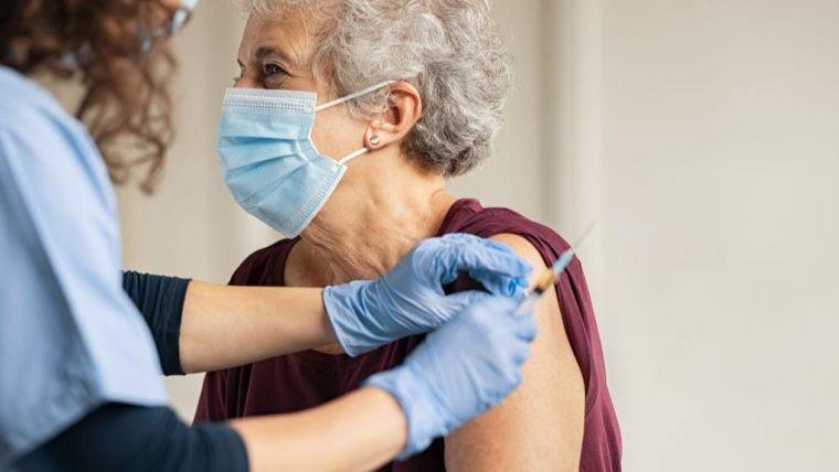 Elderly woman receiving a vaccination