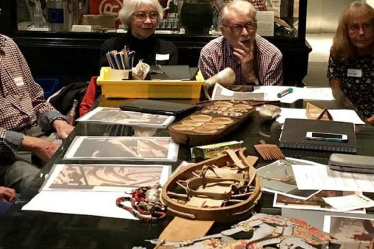 Group of older people sat around a table at Pitt Rivers Museum
