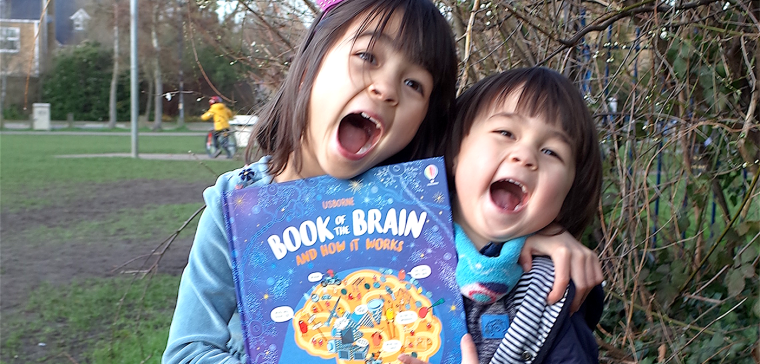 Betina Ip's daughters pictured laughing and holding a copy of Book of the Brain in the park.