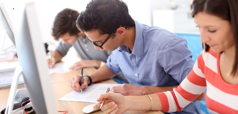 Three people completing application forms