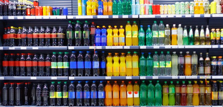 Supermarket shelf full of bottles of sugary drinks.