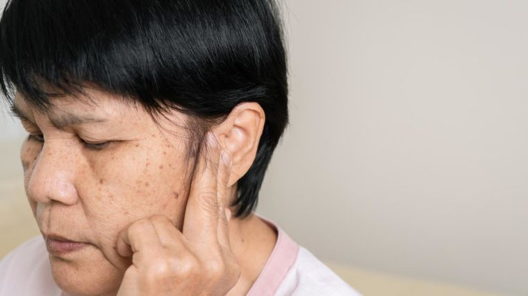 Older asian woman with ear troubles