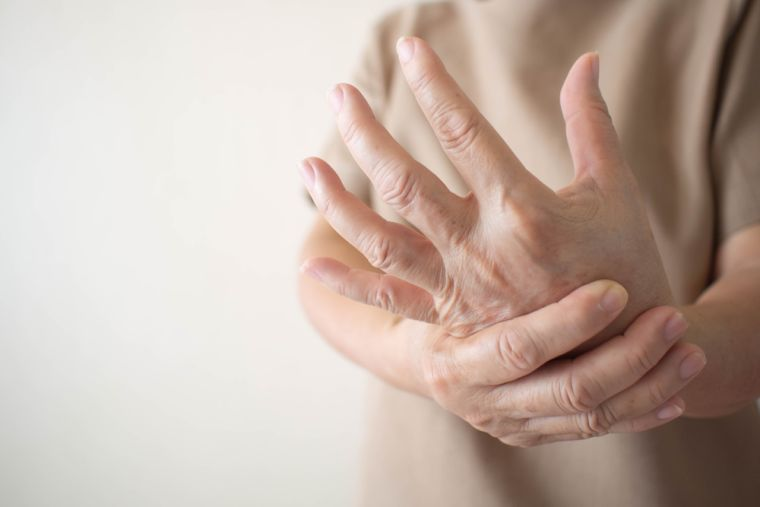 A picture of someone with rheumatoid arthritis rubbing their wrist