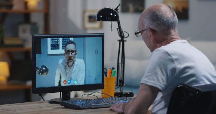 Medium shot of a disabled man talking to his doctor during a video chat