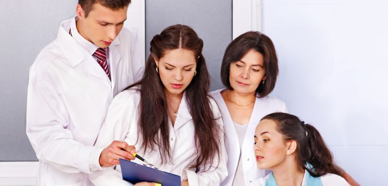 Medical students and a tutor looking at a patient chart