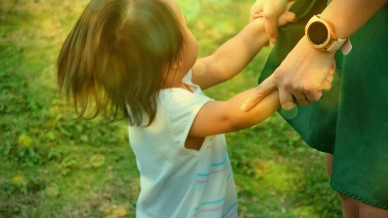 A young child in a white shirt holds and adult's hand.