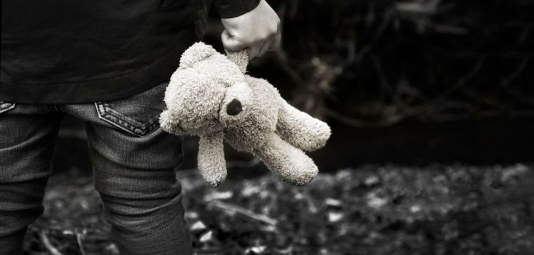 Young child holding soft toy