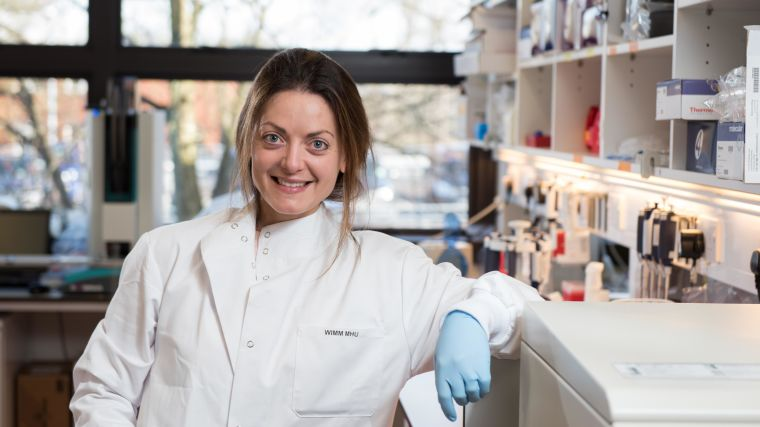 Smiling woman in lab coat in lab