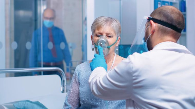 Doctor in mask helping lady with a respiratory oxygen mask sitting on hospital bed