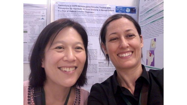 Germana Bancone and Cindy Chu, standing in front of posters at a conference