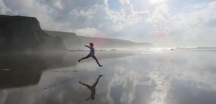Woman running on damp soil