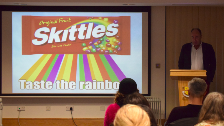 Man presenting with Skittles sweet packet on screen