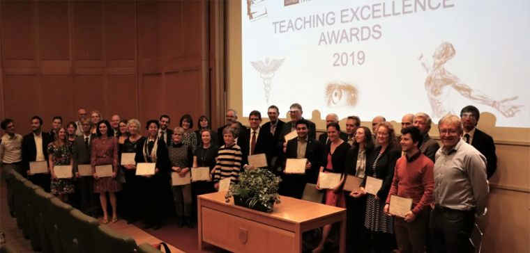 Large group of people holding certificates in front of a screen