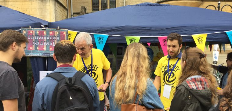 Group of young people interacting with researchers in yellow T-shirts at a street stall in Oxford