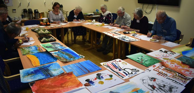 Group around table with artwork for Picturing Parkinsons