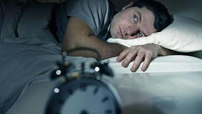 Man lying awake next to alarm clock