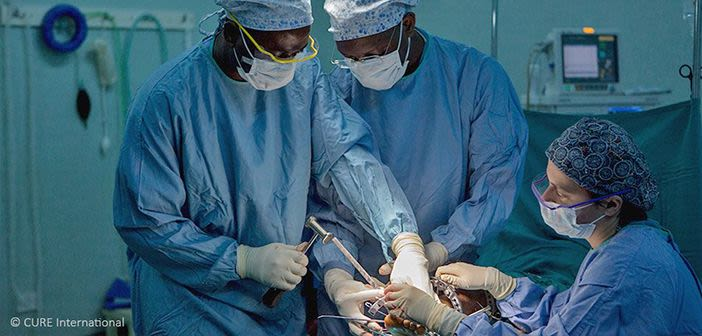 Three surgeons working in operating theatre