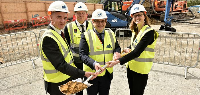 Four people in high-vis and hard hats at ground-breaking ceremony