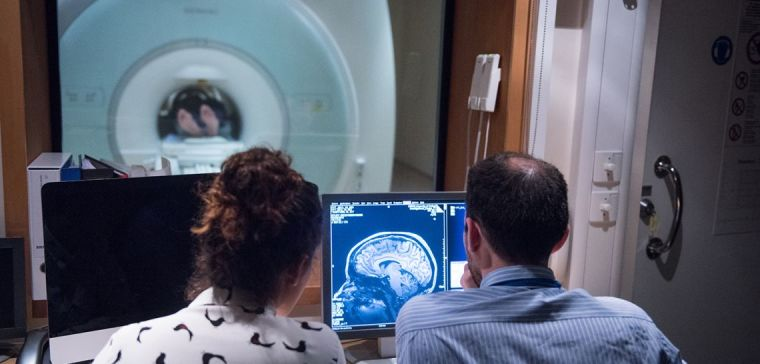 Two researchers in MRI scanner control room looking at an image on the monitor