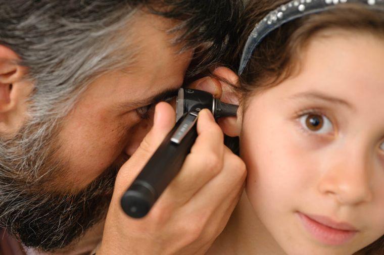 Gp checks childs ear