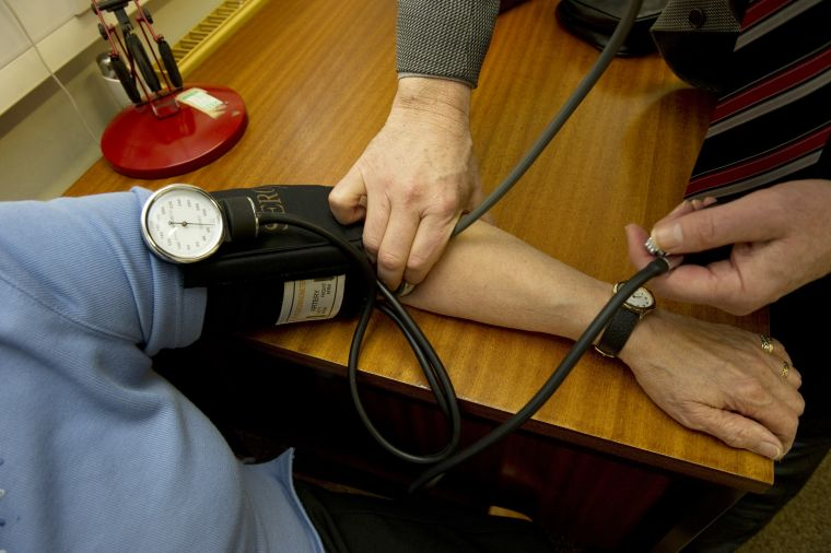 GP monitoring patient's blood pressure