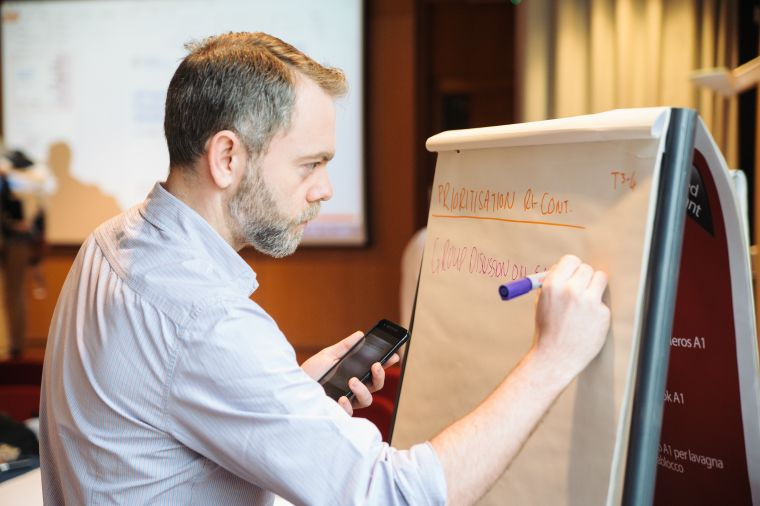 Image of a man writing on a flip chart