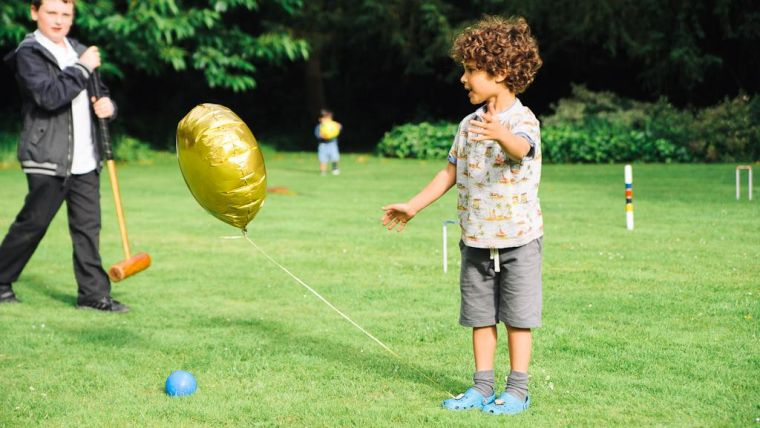 Child chases gold balloon