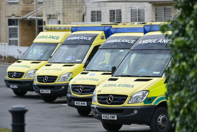 """""""We need to reduce demand on emergency services, which are currently stretched to their limit..."""" (Photo of ambulances outside the hospital)"""