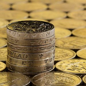 Stack of pound coins with a flat layer of coins around it