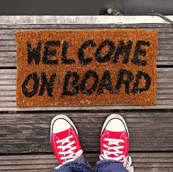 Door mat with Welcome on board written on it and a persons feet in trainers.