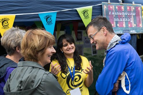 Four people talking together at an event, sign in the background