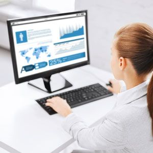 Female typing on a keyboard in front of a computer screen