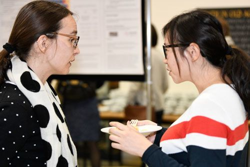 Two female researchers talking, one holding a plate