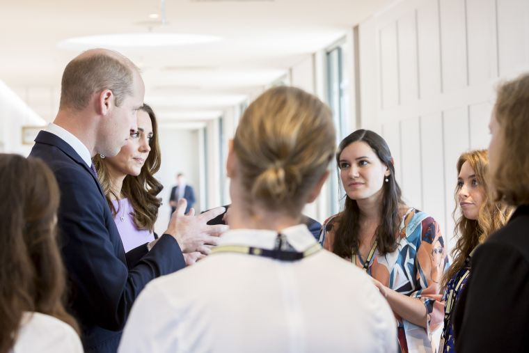 This image shows Dr Gabriela Pavarini  and the Duke & Duchess of Cambridge standing around having a conversation with people gathered around listening.