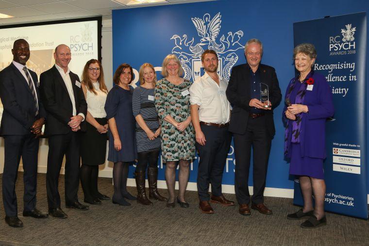 Professor Michael Sharpe holding the Psychological Medicine team award with team members and Dame Fiona Caldicott