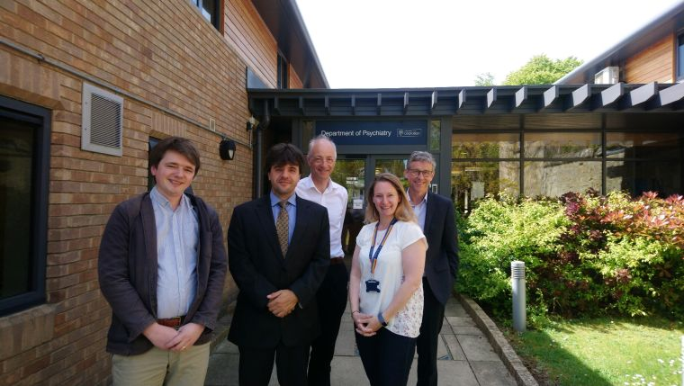 Image shows five people stood outside the department of Psychiatry, smiling at the camera.