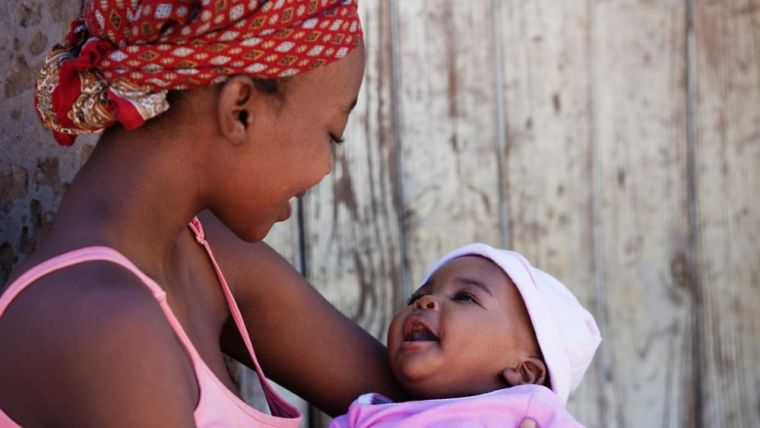 Image shows black mother holding her smiling baby.