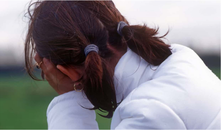 Image shows a young girl facing away from the camera with her head in her hands.
