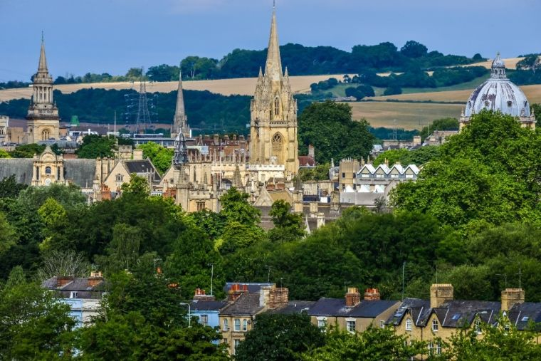 Landscape image of Oxford spires with hills in the backdrop.