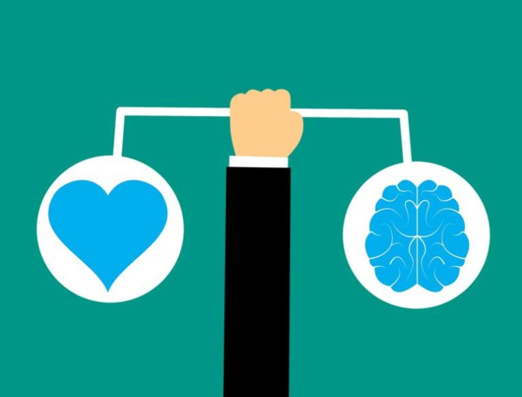 Image shows fist holding weighing scales, with a heart balanced on the left and the brain on the right.