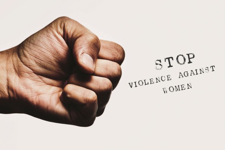 Clench fist with the words 'stop violence against women'.