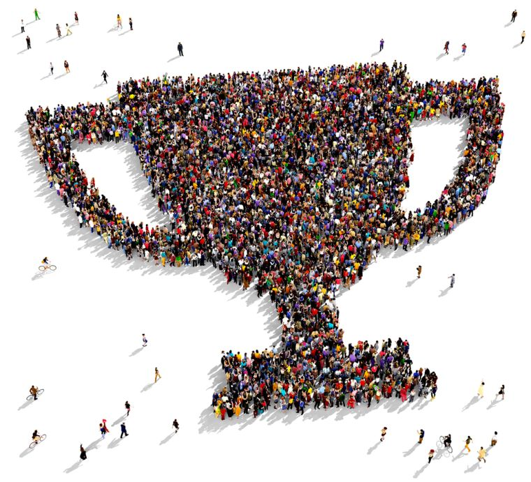 Aerial photo of a cup made out of people standing together.