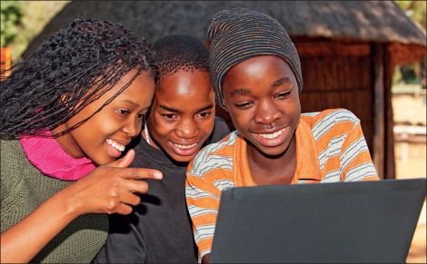 Three teenage girls looking at a laptop smiling.