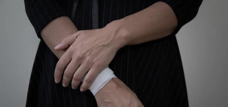 Image shows someone holding their bandaged wrist.