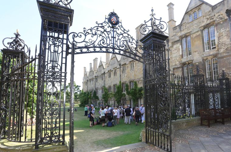 Shot through Merton College gate showing DPAG staff and students gathered in the College grounds