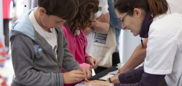 Dr Charlotte Tibbit, Research Assistant in the Liu Group, helps children to make DNA bracelets at the MRC Centenary mini-Science Festival in Oxford, June 2013