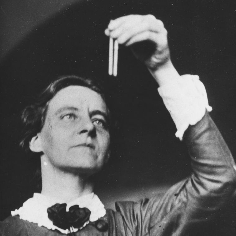 Black and white photograph of Mabel Purefoy FitzGerald examining a scientific sample in a pipette.