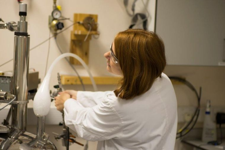 Lab Manager Vicky Ball in full PPE operating the magnets