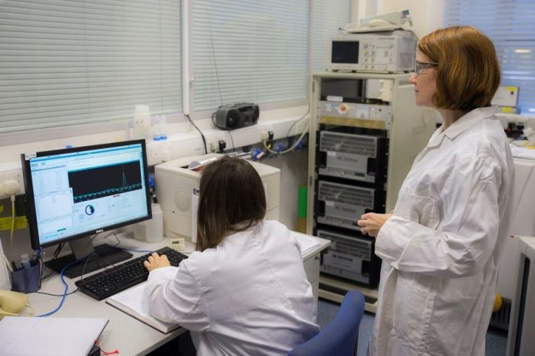 Lab manager Vicky Ball oversees a research assistant entering scan data into a computer